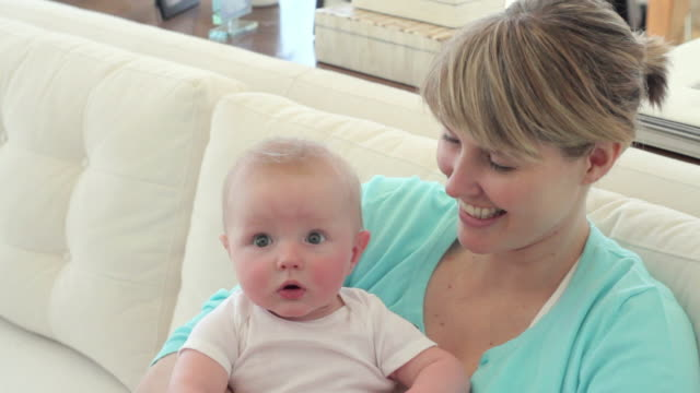 cu mother holding baby boy (2-5 months) on sofa, smiling / richmond, virginia, usa - 2 5 months stock videos & royalty-free footage