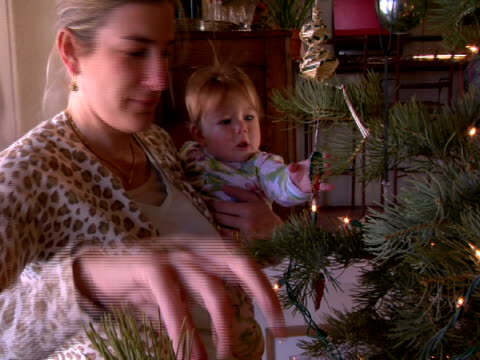 vídeos de stock e filmes b-roll de cu, pan, mother holding baby daughter (6-9 months) next to christmas tree - 6 11 meses
