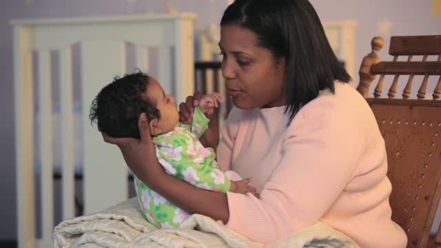 vídeos de stock e filmes b-roll de ms mother holding baby girl (2-5 months) sitting on rocking chair / richmond, virginia, usa - 2 5 meses