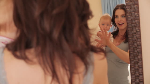 mother holding baby girl up in mirror. - 生後2ヶ月から5ヶ月点の映像素材/bロール