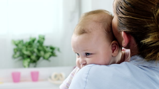 mother holding baby - over the shoulder stock videos & royalty-free footage