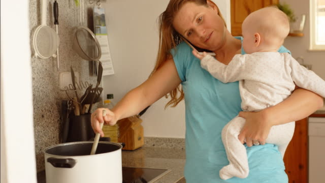 vídeos de stock, filmes e b-roll de mother holding baby while doing household chores - mil tarefas