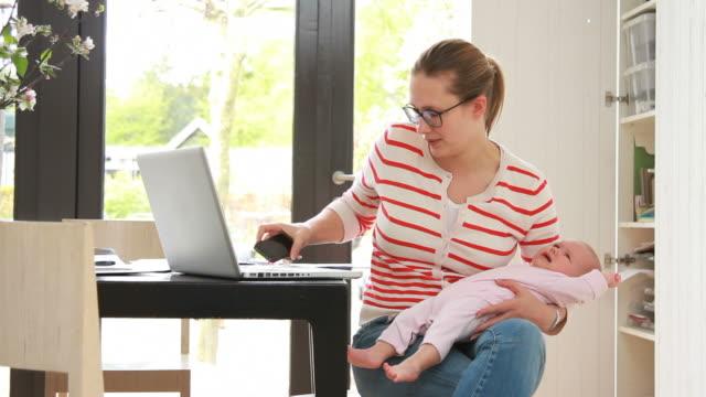 Madre con bambino lavorando da casa sul cellulare