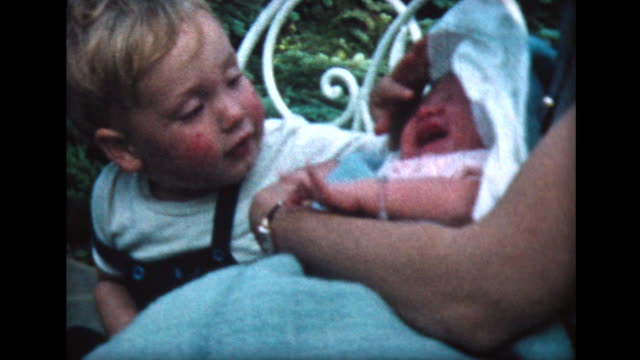 1957 mother holding baby, young boy touches baby sister's nose - baby blanket stock videos and b-roll footage