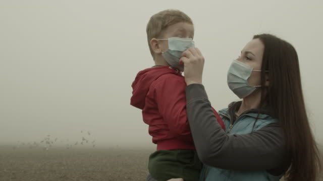 mother holding child boy and wearing face mask. - smog stock-videos und b-roll-filmmaterial