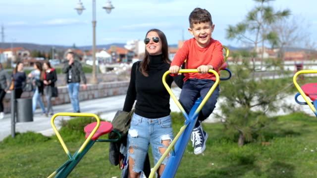 vídeos y material grabado en eventos de stock de celebración madre niños jugando en un sube y baja - balancín