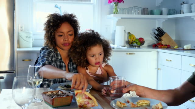 MS Mother holding daughter in lap while family dines together in kitchen