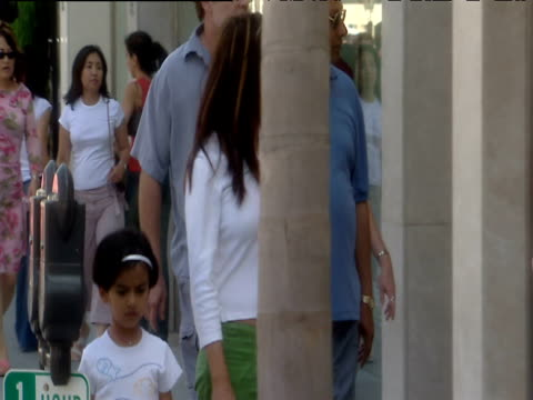 mother holding hand of daughter walks along busy pavement past shops beverly hills - two generation family stock videos & royalty-free footage
