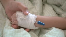 Mother holding hand of his daughter was sick in the hospital.
