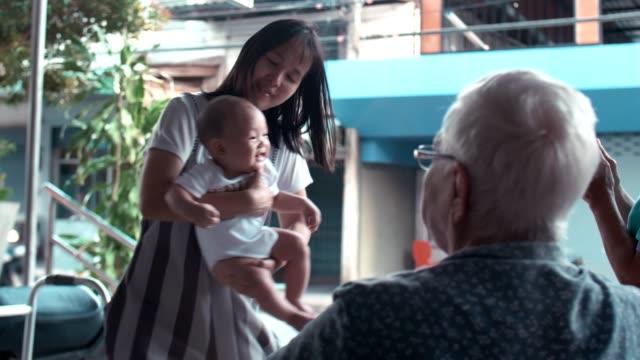 mutter hält ihren kleinen jungen und spielt mit großmutter - 6 11 months stock-videos und b-roll-filmmaterial
