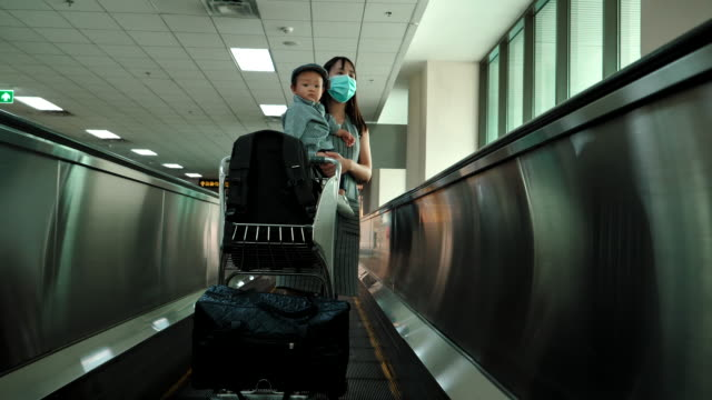 mother holding her baby boy at the airport - 6 11 months stock videos & royalty-free footage
