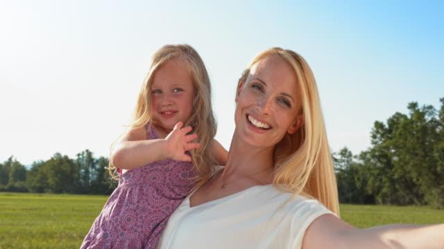 vídeos y material grabado en eventos de stock de madre sosteniendo un de san luis obispo missouri agitando hija en prado soleado - pelo rubio