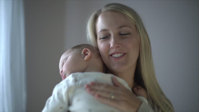cu sm mother holding her sleeping baby - child care stock videos & royalty-free footage