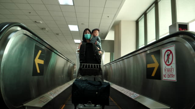 mother holding her son standing on escalator at the airport - 6 11 months stock videos & royalty-free footage