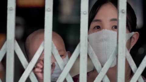 coronavirus : mother holding her son with medical mask standing behind steel door - prevention stock videos & royalty-free footage