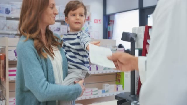 mother holding her toddler and giving her prescription to the pharmacist - chemist stock videos & royalty-free footage