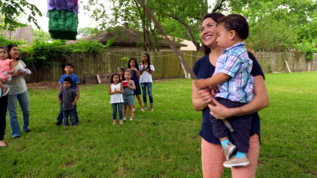 ms pan mother holding infant son up in air to swing at pinata during birthday party - papier stock videos & royalty-free footage