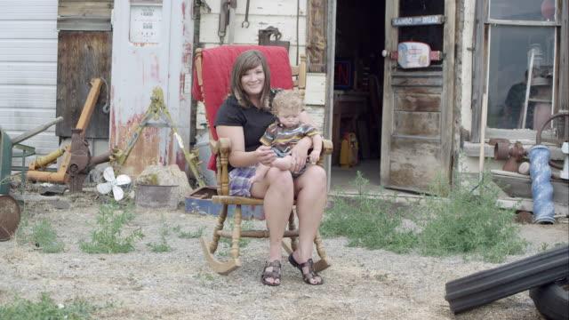 """""""mother holding son, sitting in a rocker out doors"""" - korta ärmar bildbanksvideor och videomaterial från bakom kulisserna"""