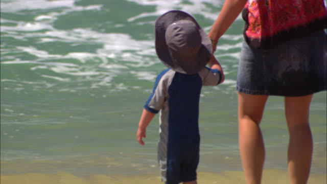 vídeos de stock, filmes e b-roll de cu mother holding son's hand and walking down from sand into ocean waves, sydney, new south wales, australia - hat