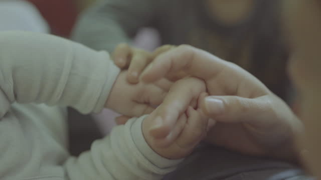 stockvideo's en b-roll-footage met mother holding the hands of a little baby - adn