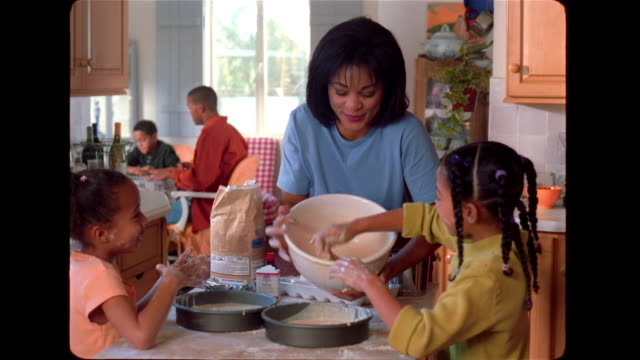 A mother holds a mixing bowl while one of her daughters scrapes the batter into a cake pan.