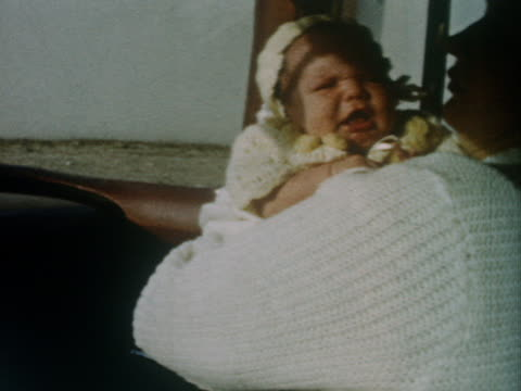 a mother holds her baby. - 1962 stock-videos und b-roll-filmmaterial