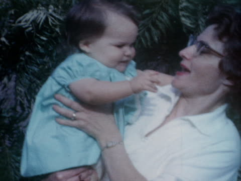 a mother holds her baby while her other daughters stand nearby. - 1962 stock-videos und b-roll-filmmaterial