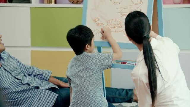 vidéos et rushes de mère homeschooling son fils dans le salon - son
