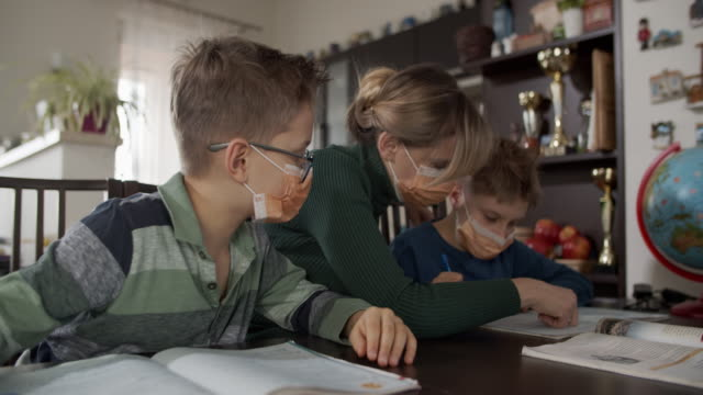mother homeschooling her sons wearing face masks - family with two children stock videos & royalty-free footage