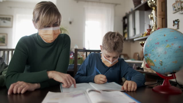 mother homeschooling her sons wearing face masks - mascherina chirurgica video stock e b–roll
