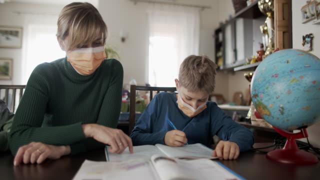 mamma homeschooling hennes söner bär ansiktsmasker - kirurgmask bildbanksvideor och videomaterial från bakom kulisserna