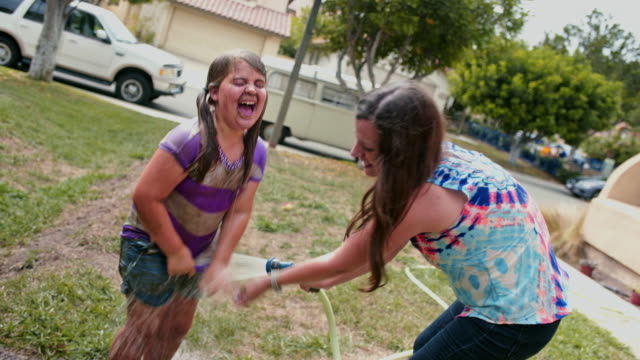 mother hoses down muddy daughter - fun times - unschuld stock-videos und b-roll-filmmaterial
