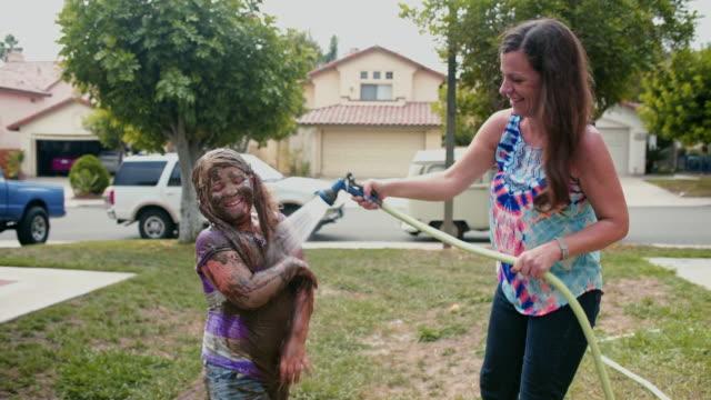 vídeos y material grabado en eventos de stock de mother hoses down muddy daughter - manguera