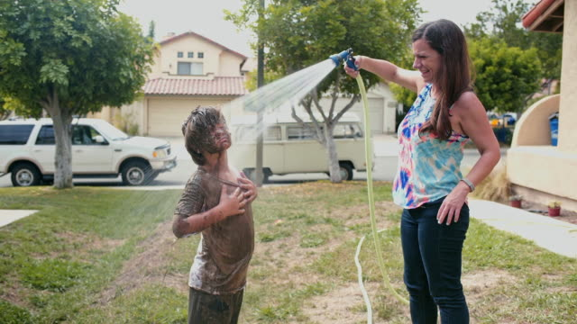 mother hoses down muddy son - unschuld stock-videos und b-roll-filmmaterial