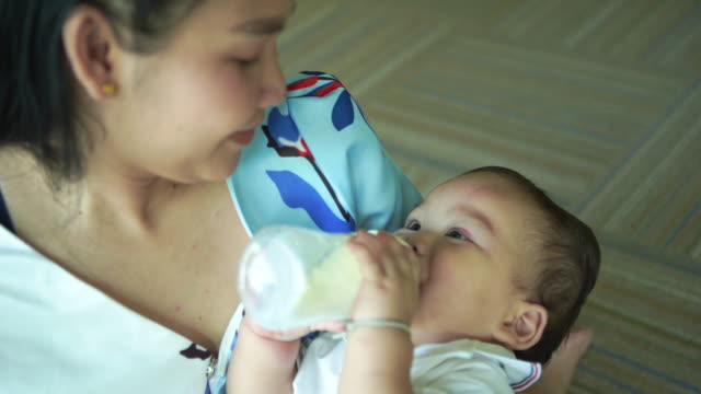 mother hug her baby boy bottle feeding milk , mother lullaby her baby for bedtime - milk bottle stock videos & royalty-free footage