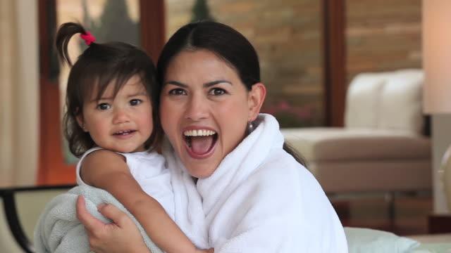 stockvideo's en b-roll-footage met cu mother hugging daughter (12-23 months), smiling / richmond, virginia, usa - in een handdoek gewikkeld