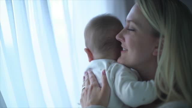 CU SM Mother hugging her baby daughter