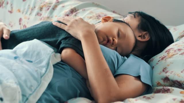 vídeos y material grabado en eventos de stock de madre abrazando a su hijo dormido. - dormitar