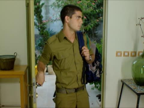 ms zo zi mother hugging soldier entering through door / beit yitzhak, israel - 建物入口点の映像素材/bロール