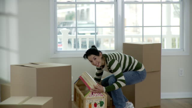 stockvideo's en b-roll-footage met ms, pan, mother hugging son (2-3) in empty room with cardboard boxes, plainfield, new jersey, usa - houten vloer
