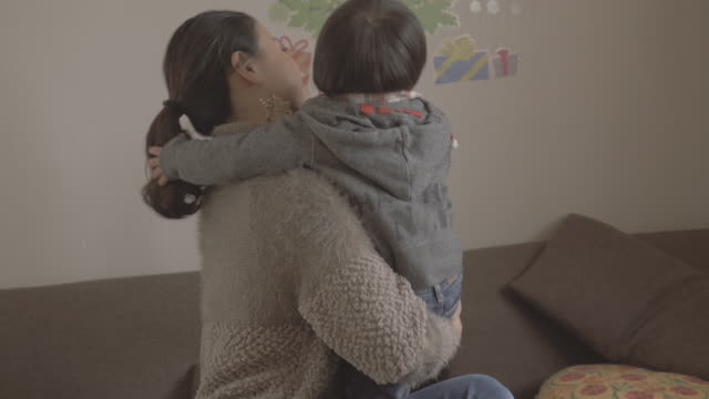 Mother hugging  son in the room