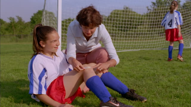vídeos de stock, filmes e b-roll de a mother hugs her daughter after placing a bandage on her knee following a soccer injury. - dano físico