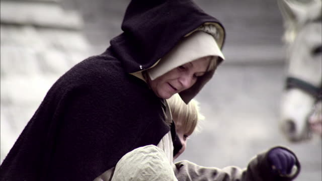 a mother hugs her daughter as they shop in a london marketplace. - historical reenactment stock videos & royalty-free footage