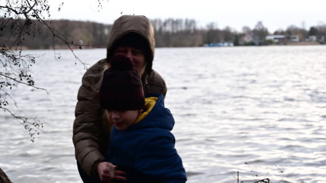 vídeos de stock, filmes e b-roll de mother hugs her son on the shore of a lake in winter. germany. brandenburg - artigo de vestuário para cabeça