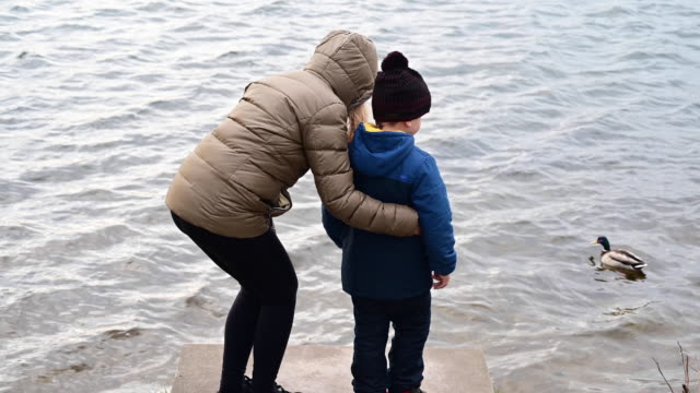 mother hugs her son on wooden pier of a lake in winter. then they leave. germany. brandenburg - warm clothing stock videos & royalty-free footage