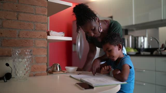 vídeos de stock, filmes e b-roll de mãe na cozinha ajudando filho em homeschooling - simplicidade