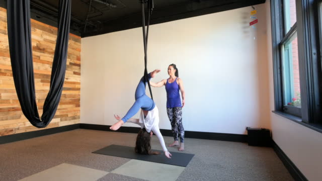 Mother instructing daughter in aerial silk yoga