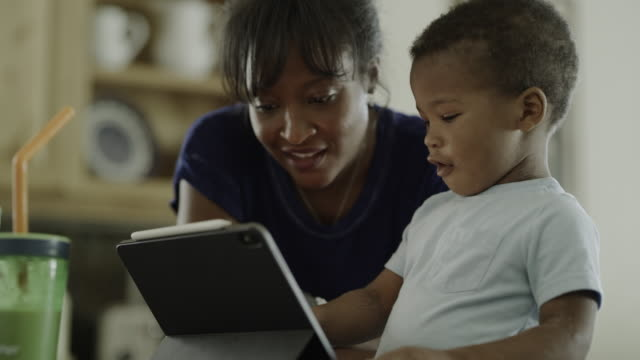mother instructing smiling son using digital tablet / orem, utah, united states - showing stock videos & royalty-free footage