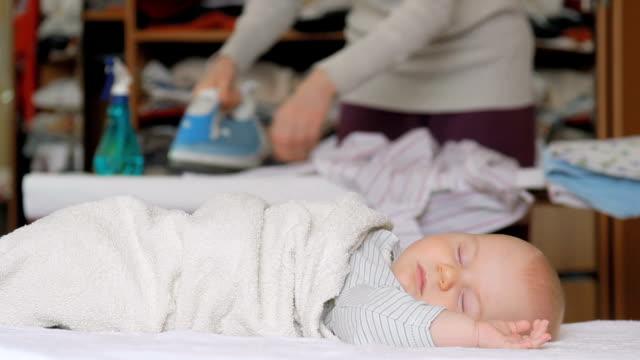 madre stira una camicia mentre il suo bambino dorme - asse da stiro video stock e b–roll