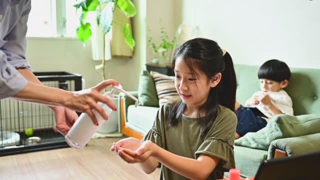 母は子供の手に消毒剤を塗っています。 - 衛生管理点の映像素材/bロール